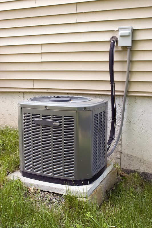 a residential central air conditioning unit sitting outside a home - Central Air Conditioner